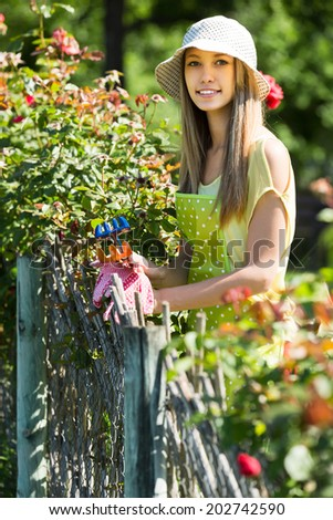 Happy woman in apron gardening with roses
