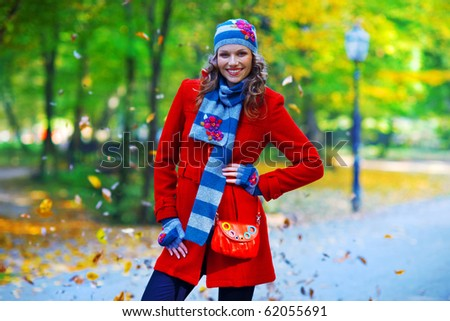 happy woman in autumn scenery in the parc - stock photo