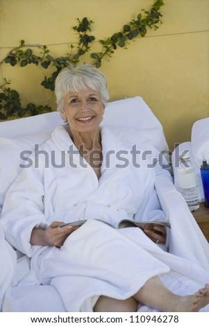 Happy woman in bathrobe - stock photo