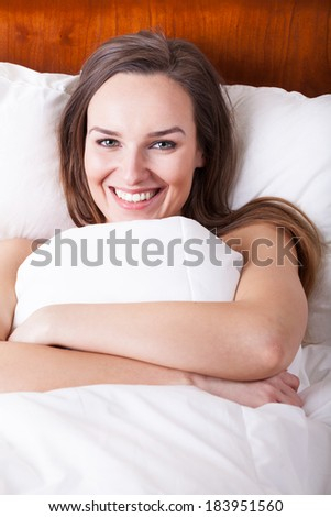 Happy woman in bed under white bedding - stock photo