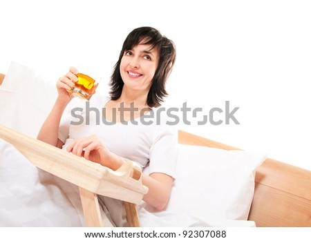 Happy woman in bed with apple juice isolated on white