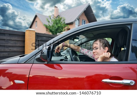 Happy woman in car looking day dreaming out of the window. Beautiful teen driver.  - stock photo