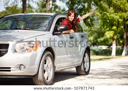 Happy woman in car waving out the window