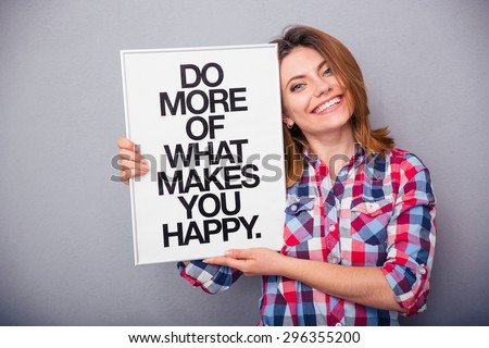 Happy woman in casual cloth holding board with motivational phrase over gray background - stock photo