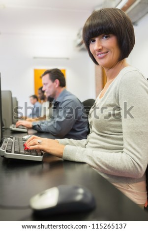 Happy woman in computer class in college