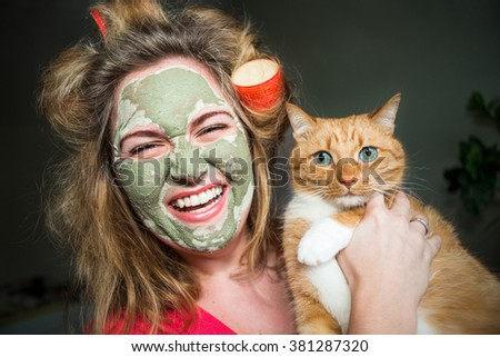 Happy woman in curlers and a mask on his face, holding a big red cat. - stock photo