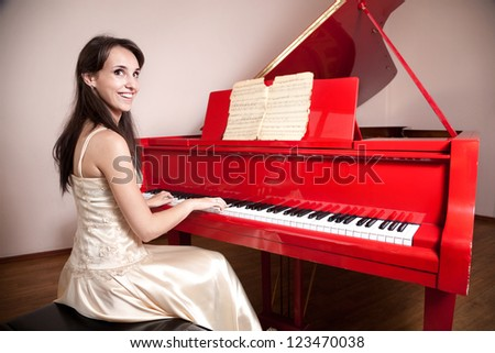 Happy woman in dress playing the red grand piano, smiling and looking at camera - stock photo