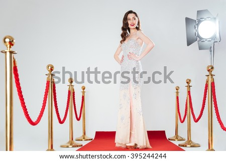Happy woman in fashion dress posing on red carpet - stock photo