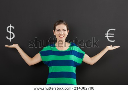Happy woman in front of a chalkboard ilustrating a concept about money currency  - stock photo