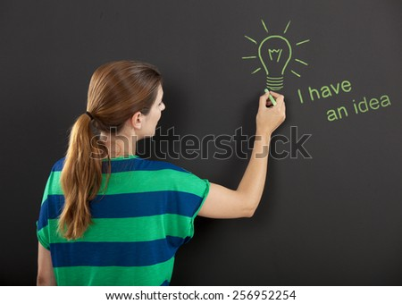 Happy woman in front of a chalkboard with a concept of having an idea design on it - stock photo