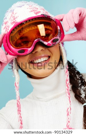 Happy woman in goggles and knitted winter cap