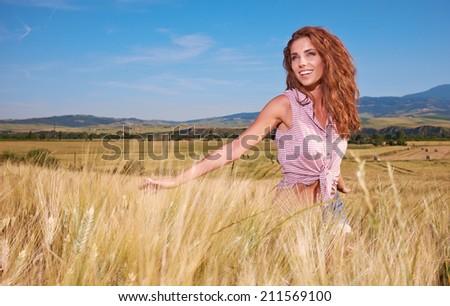 Happy woman  in golden wheat  - stock photo