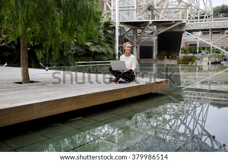 Happy woman in good mood sitting with laptop computer in hotel courtyard during her spring vacation, smiling hipster girl enjoying good day and rest after chatting with friend on portable net-book - stock photo