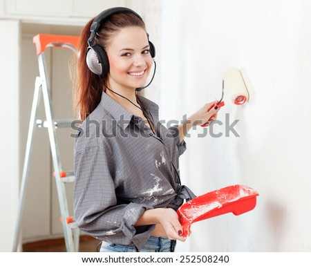 Happy  woman in headphones paints wall with roller - stock photo