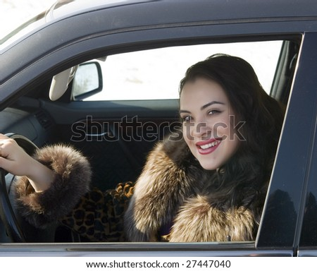 happy woman in her car - stock photo