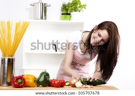happy woman in kitchen chopping cucumber - stock photo