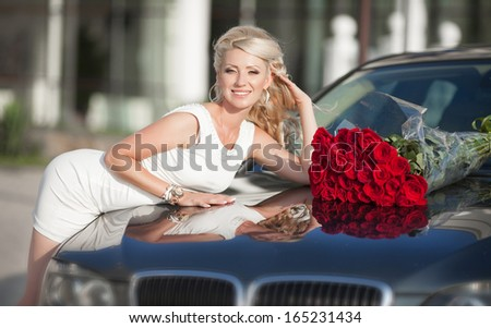 Happy woman in luxury car with roses flowers at Valentine's day. Sexy woman with bouquet in car. Beautiful rich woman smiling portrait. Sensual young girl with car. soft light shot. - stock photo