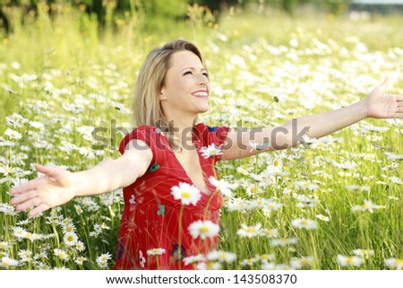 Happy woman in marguerite flower field