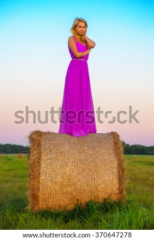 happy woman in pink dress posing  with hay in meadow field at evening time - stock photo