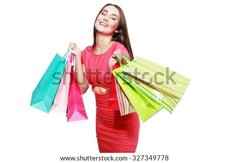 happy woman in pink summer dress smiling holding shopping bags