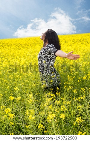 Happy woman in rapeseed field standing with hands stretched and eyes open to feel the freshness of spring - stock photo