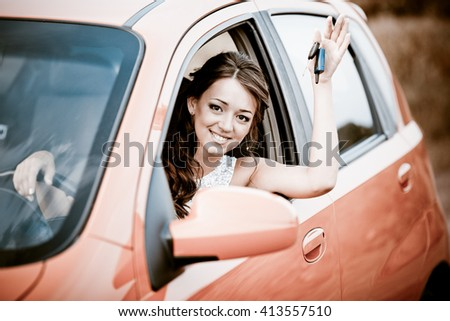 Happy woman in red car holding keys and smiling - stock photo
