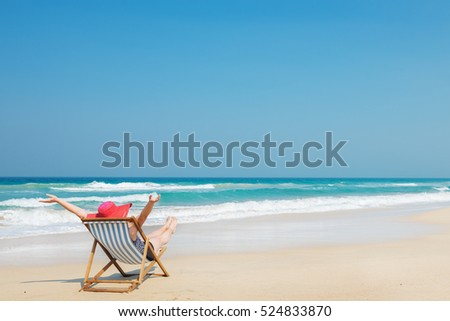 Happy woman  in red sunhat on the beach sitting on deckchair with hands up.Vacation and travel concept