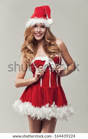 Happy woman in santa clause costume holding ribbon - stock photo