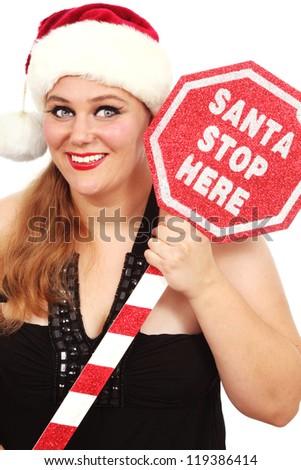 Happy woman in Santa's hat and a sign that says Santa Stop Here - stock photo