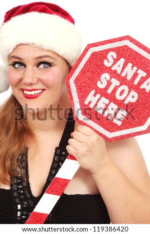 Happy woman in Santa's hat and a sign that says Santa Stop Here