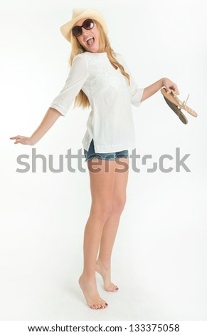 Happy woman in summer clothes holding her sandals - stock photo