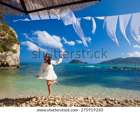 Happy woman in summer white dress on beach. Caucasian girl relaxing and enjoying peace on vacation. - stock photo
