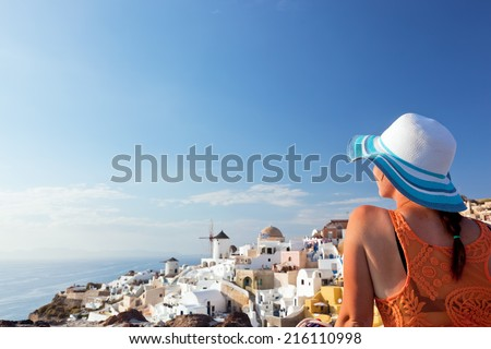 Happy woman in sun hat enjoying her holidays on Santorini island, Greece. View on Caldera and Aegean sea from Oia. Travel, tourist concepts - stock photo