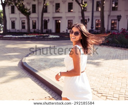 Happy woman in sunglasses and dress walking outdoors. Looking at camera - stock photo