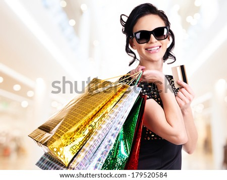 Happy woman in sunglasses with purchasing and credit card in the shop. - stock photo