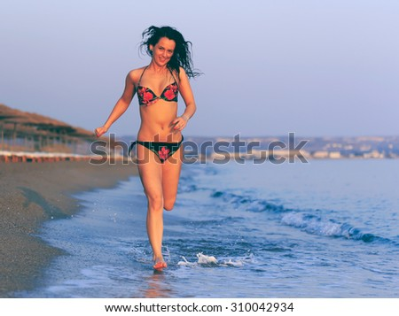 Happy woman in swimsuit running on the beach at sunrise.Vintage effect.