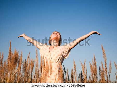 Happy woman in the field under the sunset lights. - stock photo