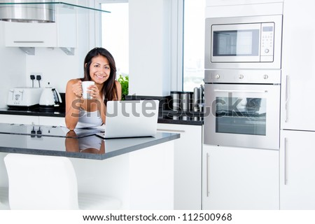 Happy woman in the kitchen reading he news on her laptop - stock photo