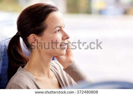 happy woman in travel bus calling on smartphone