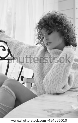 Happy woman in warm sweater with curly hair, smiling