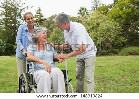 Happy woman in wheelchair with husband and daughter talking in a park