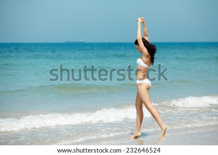 Happy woman in white bikini swimwear open her heart to sun. Vacation, beautiful sea and natural. Tan girl in summer. Perfect body shapes, relaxing soul.  - stock photo