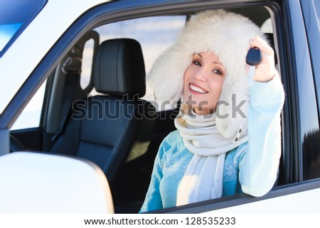 Happy woman in white fur hat in a car showing a key