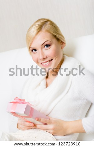 Happy woman in white sweater holds a present wrapped with pink paper and pink ribbon