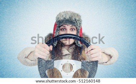 Happy Woman in winter clothes with a steering wheel, snow blizzard. Concept car driver