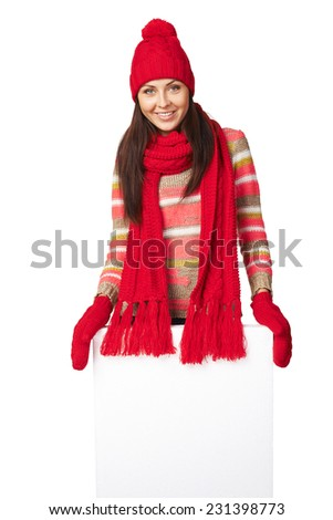Happy woman in winter outerwear standing behind and leaning on white banner at studio over white background