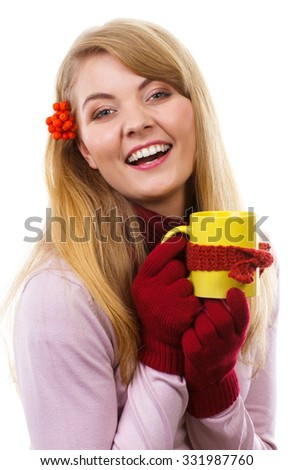 Happy woman in woolen gloves with rowan in her hair holding yellow cup of hot tea wrapped scarf, autumn decoration, warming drink, white background