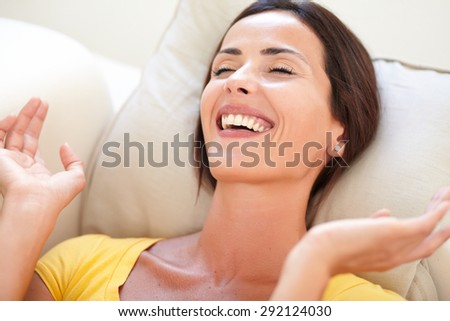 Happy woman in yellow shirt laughing with eyes closed while lying on her back - stock photo