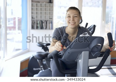 happy woman is engaged on a stationary bike