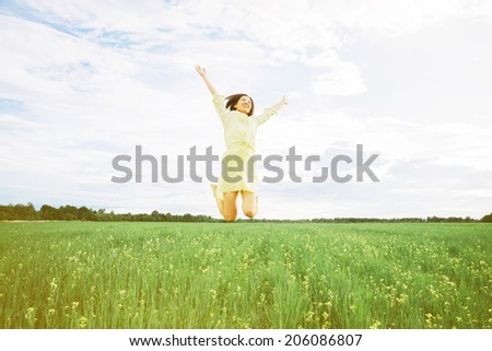 Happy woman is jumping in summer wildflower meadow
